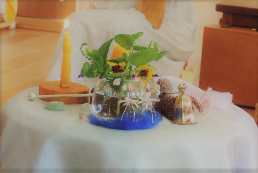 シュタイナー保育園で、一人一人の子どもの誕生日にしつらえる、お誕生日のテーブル。年齢の数のろうそくと、お花やお人形などがかわいらしく飾られています。